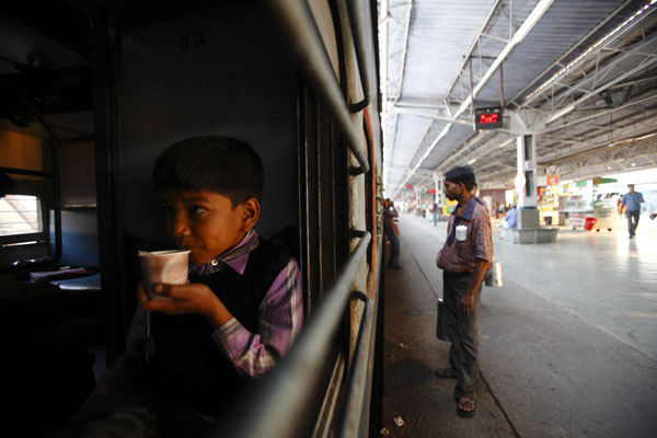 A boy haves his tea early morning inside the train at Agra Cantt Railway Station
